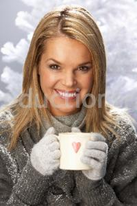 Young Woman Drinking Hot Drink Wearing Knitwear In Studio In Front Of Christmas Tree