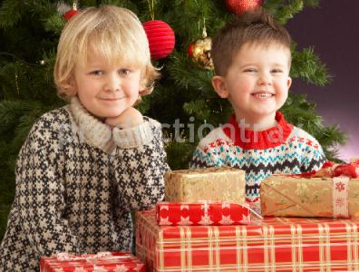 Two Young Boys With Presents In Front Of Christmas Tree