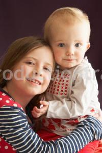 Studio Shot Of Two Sisters Hugging